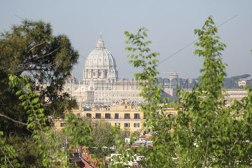 Kuppel des Petersdoms eingerahmt von gruenen Baeumen im Vordergrund