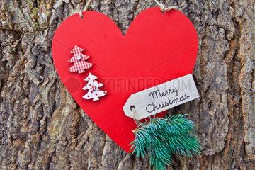 Rustikaler Hintergrund aus Rinde mit rotem Herz zu Weihnachten