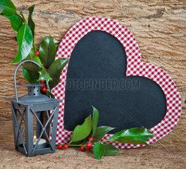 Herzfoermige Tafel  kleine Laterne mit Kerze und Stechpalmenzweige
