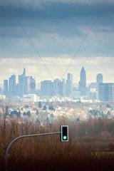 Frankfurt am Main Skylne Ansicht von Westen mit gruener Ampel im Vordergrund  Gewitterwolken am Himmel