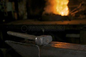 Hammer auf Amboss mit Feuer im Hintergrund