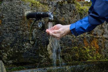Person erfrischt sich bei einer Wasserquelle
