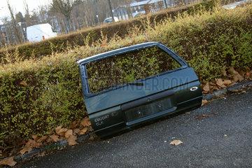 Autotuere lehnt an Hecke auf Parkplatz