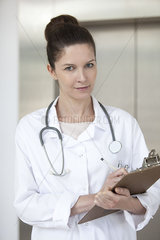Doctor writing on medical chart  portrait