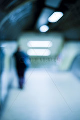Person walking alone in subway station at night  defocused