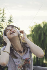 Young woman listening to music through headphones
