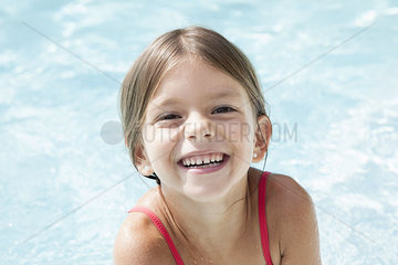 Little girl in pool  smiling cheerfully  portrait