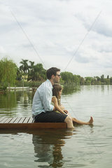 Father and young daughter sitting on dock enjoying scenery