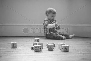 Baby boy playing on floor in nursery