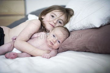 Little girl lying on bed with baby brother