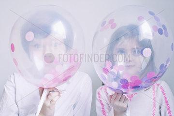 Children hiding behind transparent balloons