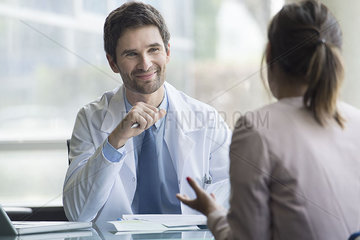 Doctor listening to patient express concerns during consultation
