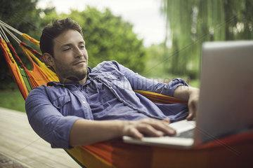 Man reclining in hammock using laptop computer