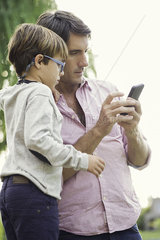 Father and young son looking at smartphone together outdoors