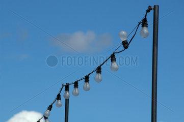 Lichterkette mit Gluehlampen vor blauem Himmel.