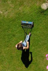 Rasenmaehen an einem sonnigen Sommertag