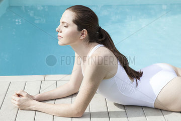 Young woman sunbathing beside pool with eyes closed