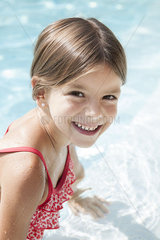 Girl in swimming pool  smiling cheerfully  portrait