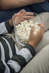 Child holding bowl of popcorn on lap  cropped