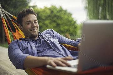 Man relaxing in hammock  using laptop computer