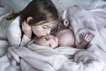 Little girl kissing baby brother's cheek on bed