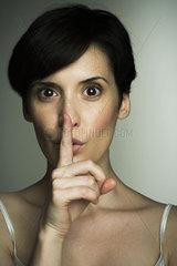 Mid-adult woman making shush gesture