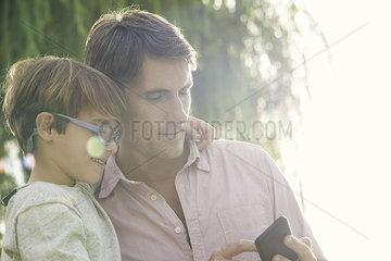 Father and son looking at smartphone outdoors  overexposure