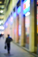 Pedestrian walking on sidewalk at night  defocused
