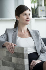 Woman relaxing in arm chair looking away contemplatively