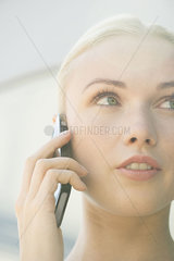 Woman talking on cell phone with serious expression on face