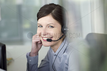 Businesswoman wearing headset during conference call  portrait