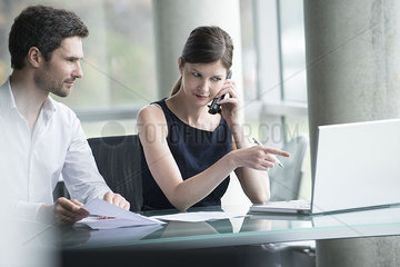Businesswoman directing colleague's attention to computer screen