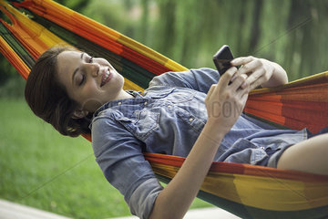 Woman relaxing in hammock with smartphone