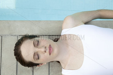 Young woman sunbathing by pool with eyes closed  overhead view