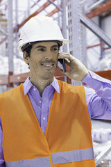 Worker using cell phone at industrial site