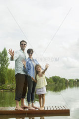 Family standing on dock waving
