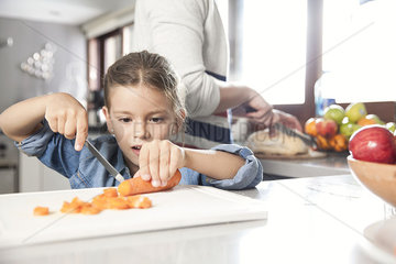 Little girl helping to prepare food in kitchen
