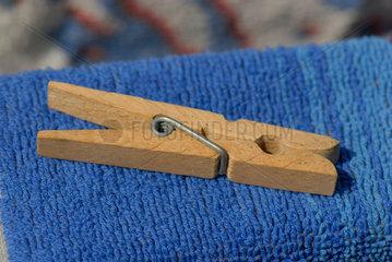 Waescheklammer aus Holz liegt auf blauem Badetuch.