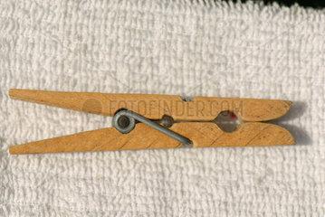 Waescheklammer aus Holz liegt auf weissem Badetuch.