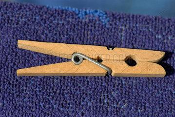 Waescheklammer aus Holz liegt auf baluem Badetuch.