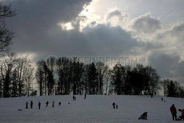 Winterlandschaft mit Schlitten- und Skifahrern