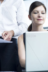 Woman working on laptop computer  boss watching over her shoulder