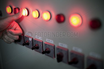 Worker pressing illuminated buttons on industrial control panel