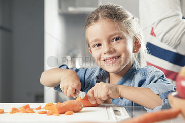 Little girl slicing carrots in kitchen  portrait