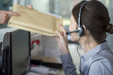 Receptionist receiving mail from delivery person
