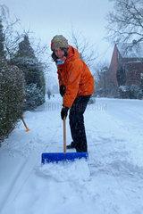 Frau beim Schneeschieben