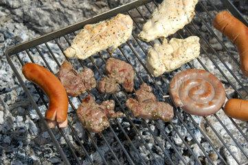 Fleisch und Wuerste auf Grill.
