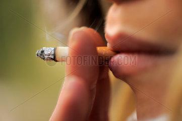 Junge Frau raucht eine Zigarette.