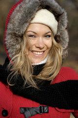 Lachende junge Frau in Winterkleidern.