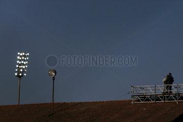 Kameramann auf Stadiondach  Flutlicht